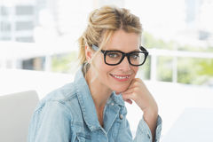 Blonda märkes- bärande exponeringsglas som ler på kameran Royaltyfri Foto