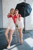 Blonda modeller för i kulisserna fotografikamratskap royaltyfri foto