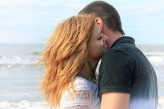 Blonda och för brunett tonåriga par kramar tillsammans i stranden som är utomhus- på sommarsemestern Arkivfoto