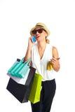 Blonda shopaholic kvinnapåsar och smartphone Royaltyfri Foto