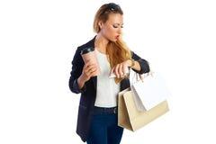Blonda shopaholic kvinnapåsar och smartphone Arkivfoton