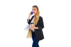 Blonda shopaholic kvinnapåsar och smartphone arkivfoto