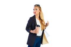 Blonda shopaholic kvinnapåsar och smartphone royaltyfria foton
