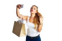 Blonda shopaholic kvinnapåsar och smartphone fotografering för bildbyråer