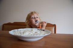 Blonda små behandla som ett barn äta frukosten Arkivfoto
