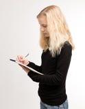 Blonda tonåriga flickahandstilanmärkningar på notepaden Arkivfoton