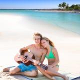 Blonda turist- par som spelar gitarren på stranden Arkivfoton