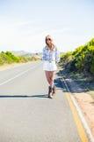 Blonde à la mode avec des lunettes de soleil faisant de l'auto-stop Image stock
