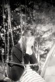 Blonde à la mode gaie sur le carrousel Émotions de tristesse et de peine Photographie stock