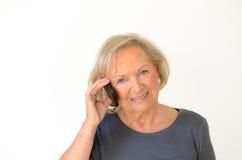 Blonde ältere Frau, die ein Gespräch auf Mobile hat Lizenzfreie Stockbilder