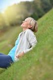 Blonde ältere Frau, die im Gras sich entspannt Stockfotografie