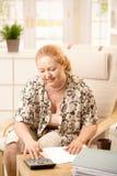 Ältere Frau, die zu Hause berechnet Stockbild