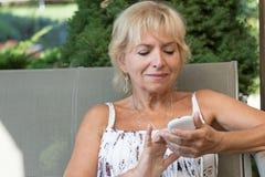 Blonde ältere Frau mit intelligentem Telefon draußen Lizenzfreies Stockfoto