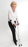 Blonde ältere Frau mit Krücken Lizenzfreie Stockbilder