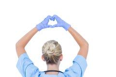 blonde Ärztin, die ein Heidezeichen tut Stockfotos