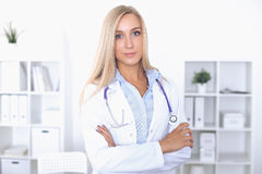 Blonde Ärztin, die am Tisch im Krankenhaus sitzt und Kamera betrachtet Stockfoto
