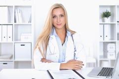Blonde Ärztin, die am Tisch im Krankenhaus sitzt und Kamera betrachtet Lizenzfreie Stockfotografie