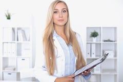 Blonde Ärztin, die am Tisch im Krankenhaus sitzt und Kamera betrachtet Stockbilder