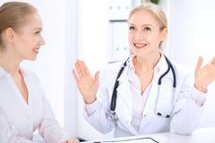 Blonde Ärztin und Patient, die im Krankenhausbüro spricht Gesundheitswesen und Kundenservice in der Medizin Stockbild