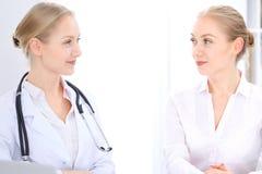 Blonde Ärztin und Patient, die im Krankenhausbüro spricht Gesundheitswesen und Kundenservice in der Medizin Lizenzfreie Stockbilder