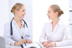 Blonde Ärztin und Patient, die im Krankenhausbüro spricht Gesundheitswesen und Kundenservice in der Medizin Stockfoto