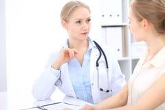 Blonde Ärztin und Patient, die im Krankenhausbüro spricht Gesundheitswesen und Kundenservice in der Medizin Stockfotos