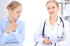 Blonde Ärztin und Patient, die im Krankenhausbüro spricht Gesundheitswesen und Kundenservice in der Medizin Stockfotografie