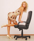 Blonde. Young beautiful blonde with leather armchair Royalty Free Stock Images