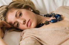 Blonde. Beautiful young blonde in bed in a tan knit blouse Royalty Free Stock Images