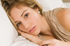 Blonde. Beautiful young blonde in bed in a tan knit blouse Stock Photos