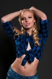 Blonde. Blue eyed blonde in a plaid shirt and denim shorts royalty free stock images