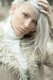 Blonde. Portrait of a beautiful girl wearing white fur in the fresh air stock photos