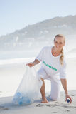 Blonde activist picking up trash on the beach Stock Image