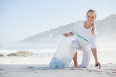 Blonde activist picking up trash on the beach Stock Photos