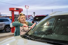 Blonde adult woman washes the windshield with a Squeegee while filling up the car with gas at a gas. Station stock image