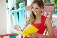 Blonde affichant le livre intéressant Photo stock