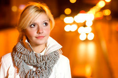 Blonde against night city. Fair-haired girl smiles against night road with motor transport Royalty Free Stock Image