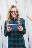 Blonde alegre con los vidrios usando la PC de la tableta Imágenes de archivo libres de regalías