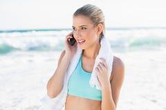 Blonde alegre del ajuste en ropa de deportes en el teléfono Foto de archivo