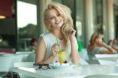 Blonde alegre joven en una barra de la bebida Imagenes de archivo