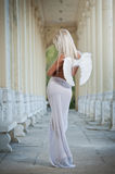 Blonde angel with white light wings and white veil posing outdoor Royalty Free Stock Photo