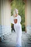 Blonde angel with white light wings and white veil posing outdoor Royalty Free Stock Photography