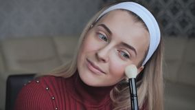 Blonde applying facial powder to herself with a brush. Blonde applying facial powder to herself with a brush stock video