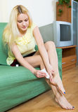 Blonde applying gel over heel foot bruise at home Stock Photos