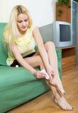 Blonde applying gel over heel foot bruise at home Stock Photos