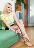 Blonde applying gel over heel foot bruise at home Royalty Free Stock Photos
