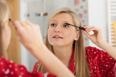 Blonde applying mascara Royalty Free Stock Photos
