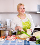 Blonde in apron with meat Royalty Free Stock Image