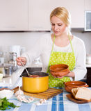 Blonde in apron with meat Stock Photo