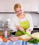 Blonde in apron with meat Stock Photos